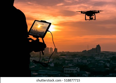 Silhouette of Man using drone to monitor the city at the evening, city sunset background.