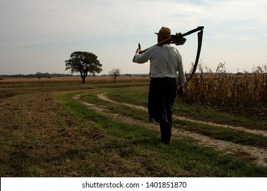 Silhouette of a Man in a village with a scythe backlight. Large manual harvesting scythe on backlight. Portrait of an man with scythe with a meadow and tree on background.