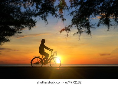 Silhouette man and vintage bike relaxing with sun  effect on sunrise time at beach.