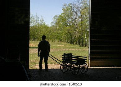 silhouette of man and wagon