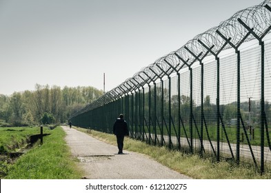 Silhouette of man walking along a barbed wire high fence