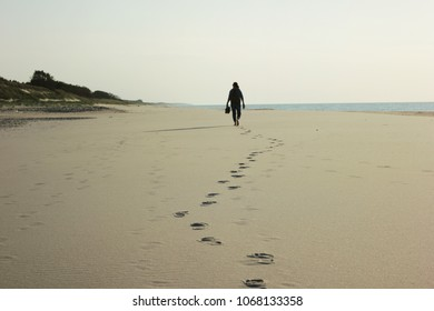 Silhouette of a man walking along the beach