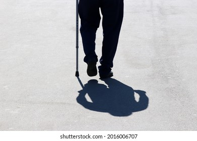Silhouette of man walking with a cane down the street, shadow on asphalt. Concept of old age, diseases of the spine or joint disease, elderly people
