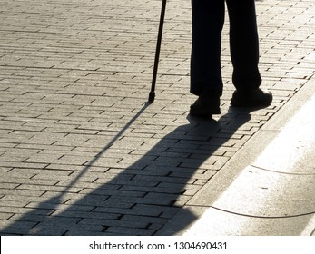 Silhouette of man walking with a cane, long shadow on pavement. Concept of lame or blind person, disability, old age, diseases of the spine