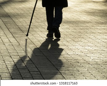 Silhouette of man walking with a cane, long shadow on pavement. Concept of blind person, limping, disability, old age, diseases of the spine