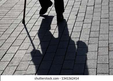 Silhouette of man walking with a cane, long shadow on pavement. Concept of lame or blind person, disability, old age, poverty, diseases of the spine
