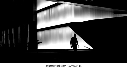 Silhouette of a man walking the city street stairs in front of modern building in central business district in late night hours