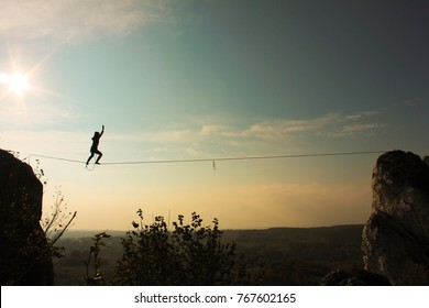 Silhouette of man walking on slackline / tight rope with sky and beautiful landscape in the background.