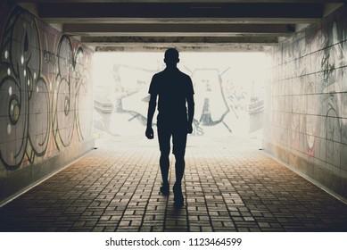 silhouette of a man walking on an underground pedestrian crossing