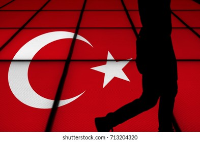 Silhouette of a man walking past a light box illuminating a Turkey flag.