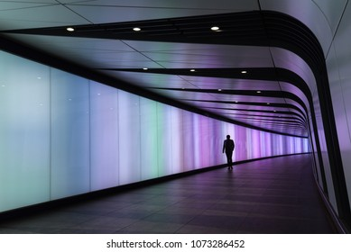 Silhouette of man walking through multi colour tunnel