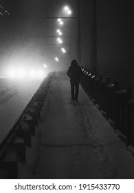 silhouette of a man walking through a snow-covered city in a heavy snowstorm, black and white photo