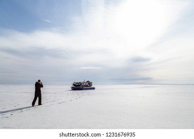 A silhouette of the man walking towards the Hovercraft on the ice covered lake Baikal, Siberia, Russia