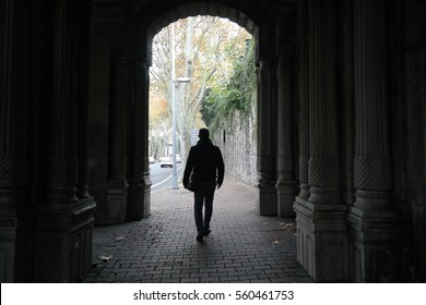 Silhouette of Man Walking in Tunnel. Light at End of Tunnel.
