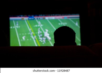 Silhouette of Man Watching Football Game on Widescreen TV