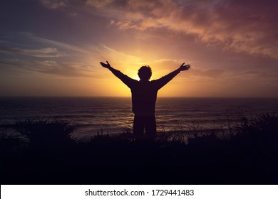 Silhouette Of A Man Watching orange Sunset on cliff over the sea with open arms