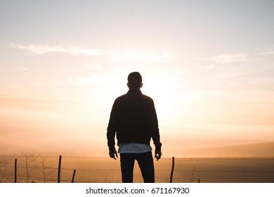 Silhouette man watching sunrise