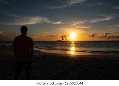 Silhouette of a Man Watching Sunset Over the Ocean with a Sailboat Passing the Horizon