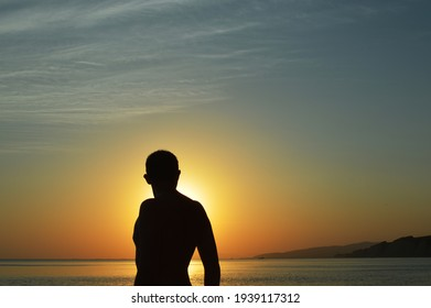 Silhouette of man watching sunset over the sea. Male silhouette and sea sunset.