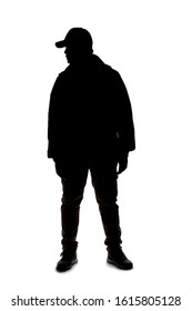 Silhouette of a man wearing a backpack looking like a traveler or hiker trekking.  He is patiently standing and waiting
