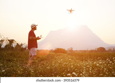 Silhouette of a man web author is taking photo of a beautiful wild nature on flying go pro camera for his travel web page. Male tourist is shooting video on radio controlled drone during summer trip