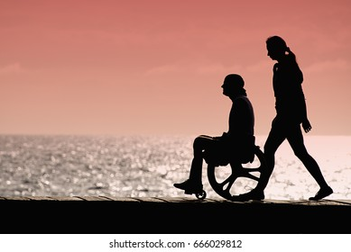 Silhouette of a man in a wheelchair with a woman at sunset at sea, draw rights in a wheelchair