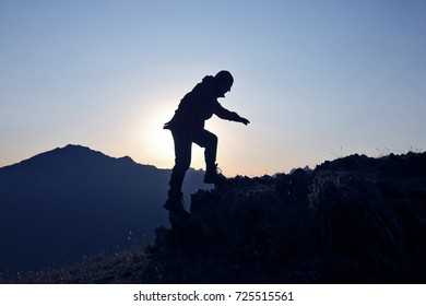 silhouette of a man who climbs the mountain on a background of dawn