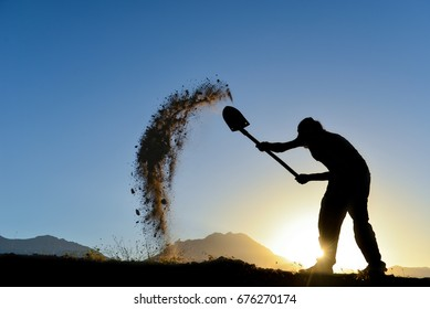 silhouette of a man who the soil with a shovel
