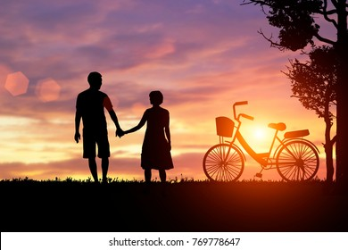 The silhouette of the man and woman hold hands together. The concept is loved by the lover, with a shared bicycle.