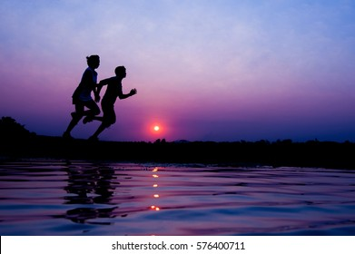Silhouette of man and woman running together on a sunset on lake coast.