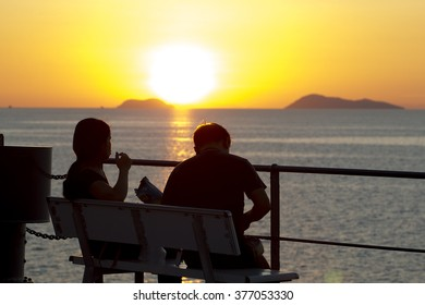 Silhouette of man and woman sitting and watching sunset on top of ferry boat.