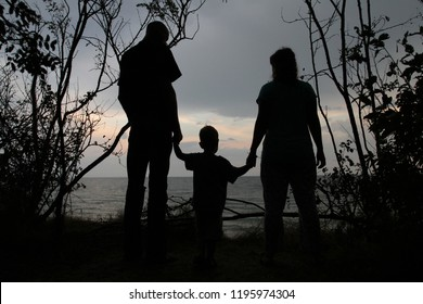 Silhouette of a man, a woman and a small child on the background of a sea sunset. Family with a baby are standing on the seashore in a frame of bushes, black silhouette
