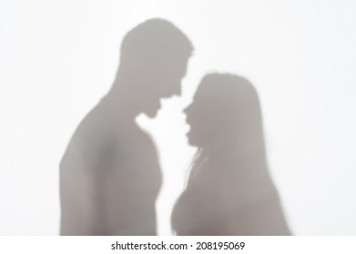 Silhouette of man and woman standing on white background and quarrelling