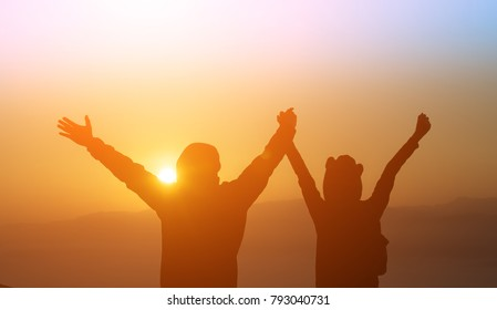 Silhouette of man and woman are standing on top of the mountain with raised hands relaxing with sunrise by nature at sunrise ,Life style,Happy couple in love at sunrise or sunset,First morning light,