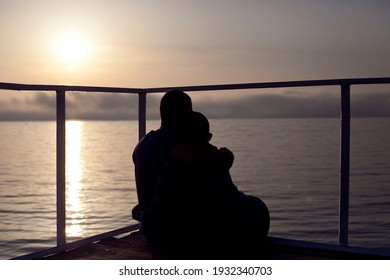 Silhouette of a man and a woman at sunset by the sea