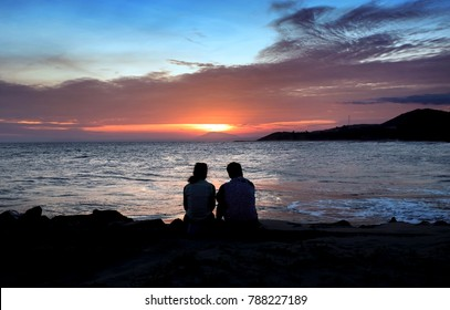 Silhouette of man and woman watching the sunset