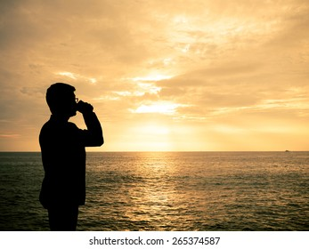 Silhouette man zipping coffee at sunset beach