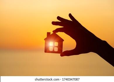 la silhouette de la main de l'homme tenant une petite maison en bois contre le coucher ou le lever du soleil, le concept de maison et de famille, énergie solaire, agent immobilier offre une nouvelle maison à louer ou à acheter, copier l'espace