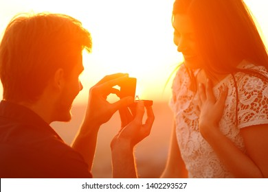 Silhouette of a marriage proposal of woman and man at sunset