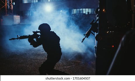 Silhouette of Masked Team of Armed SWAT Police Officers Exit a Black Van Parked Outside of an Office Building. Soldiers with Rifles and Flashlights Run on a Street Filled with Smoke.