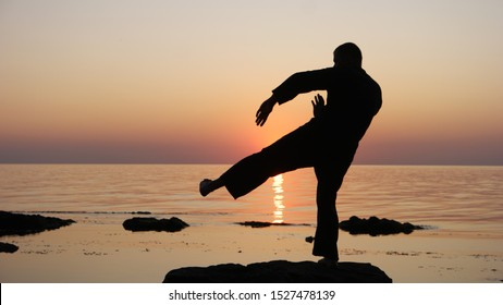 Silhouette of a Master Wing Chun on a background of sea sunset. Defense and counterattack by foot