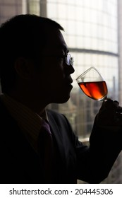 Silhouette of mature businessman drinking a glass of wine in hotel.