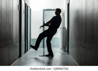 Silhouette Of A Mature Man Falling While Mopping Floor In The Corridor