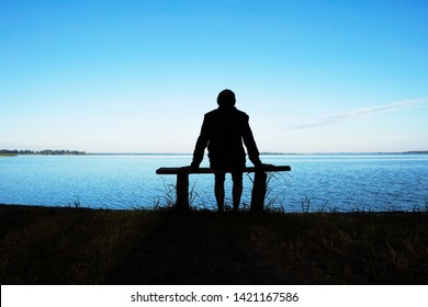 Silhouette of a meditating man 58 years old at dawn on Svityaz Lake in Ukraine. The man is sitting on a home-made wooden bench.