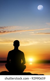 Silhouette of the meditating person against a sea decline