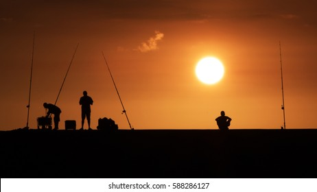 Silhouette of men with fishing pole with sunset background