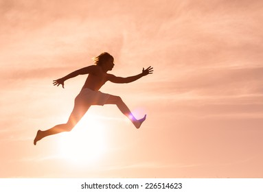 Silhouette of men jumping through the air