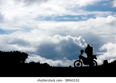 silhouette men near motorcycle on background of the sky