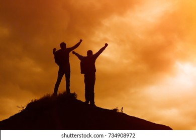 Silhouette of men standing on the top of a hill.