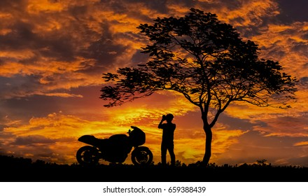 Silhouette, Men Take a photo of the sunset gold color and motorbike Big Bike, beautiful.